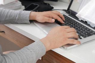 ラップトップ コンピューターを使用してテーブルに座っている人 - No.1152482