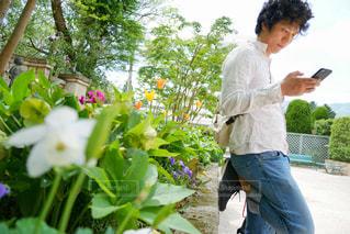 花壇近くにいるスマホ(スマートフォン)をいじる若い男性の写真・画像素材[1167543]
