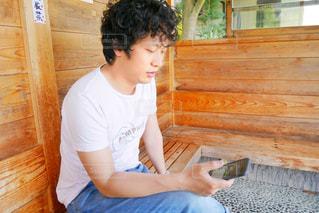 木製のベンチ上に座ってスマホを操作してる男の写真・画像素材[1167627]