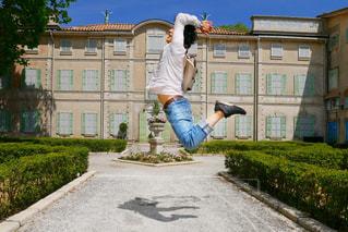 建物の前で海老反りジャンプをする男性の写真・画像素材[1190545]