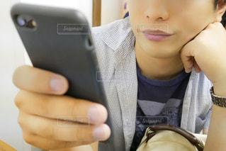 携帯電話を保持している男性の写真・画像素材[1239334]