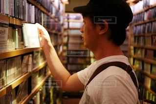 本の棚の前に立っている人の写真・画像素材[1239410]