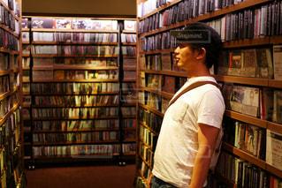 本の棚の前に立っている人の写真・画像素材[1239412]