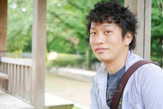 フェンスの前で微笑む男の写真・画像素材[1270352]