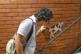 れんが造りの壁の横に立っている男性の写真・画像素材[1276622]