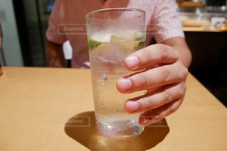 テーブルの上にある、ガラスのかぼす酒のお酒の写真・画像素材[1302089]