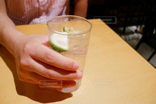 テーブルにビールのグラスを持っている手の写真・画像素材[1302091]