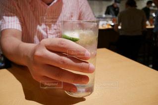 テーブルの上にある、ガラスのかぼす酒のお酒の写真・画像素材[1302092]