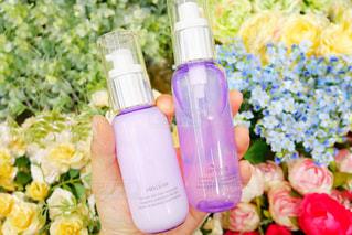 近くの花を保持しているプラスチック製の化粧品の写真・画像素材[1328605]