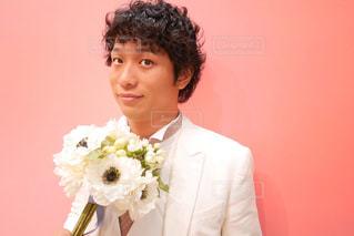 花を保持しているスーツを着てる新郎の写真・画像素材[1341874]