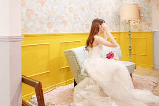 ソファの上に座っているウェディングドレスの女性の写真・画像素材[1355424]