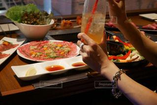 テーブル前でドリンクを持っている女性の腕の写真・画像素材[1374397]