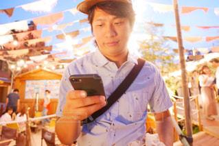 イベント会場で携帯電話を持っている男性の写真・画像素材[1399766]
