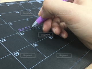 スケジュール表に書く手元の写真・画像素材[1414344]