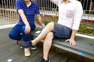 フェンスの横にあるベンチに座っている人の写真・画像素材[1521455]
