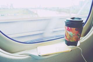 近くの車窓にあるスマホとカップの写真・画像素材[1532532]