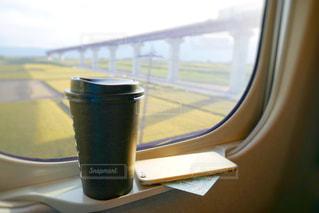 ウィンドウの横にあるコーヒー カップの写真・画像素材[1532725]