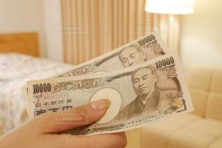 ホテルのベッドルームで現金をもらう女性の手の写真・画像素材[1533610]