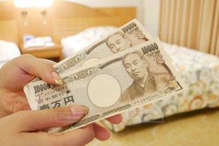 ホテルのベッドルームで現金をもらう女性の手の写真・画像素材[1533613]