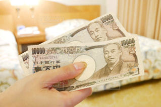 ホテルのベッドルームで現金をもらう女性の手の写真・画像素材[1533615]