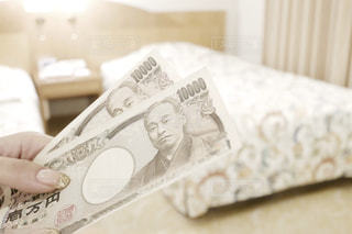 ホテルのベッドルームで現金をもらう女性の手の写真・画像素材[1533616]