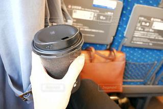 新幹線に乗り、カフェラテを飲む女性の手の写真・画像素材[1543644]