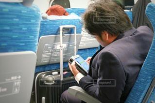 新幹線で荷物のバッグを持ってスマホを操作する男性の写真・画像素材[1550624]