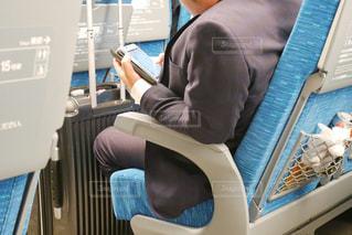 ラップトップを使用してテーブルに座ってスマホ操作する男性の写真・画像素材[1550625]
