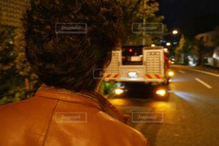 レッカー車に乗った故障車を見送る男性の写真・画像素材[1561229]