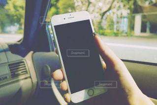 車内でスマホ操作をする女性の手の写真・画像素材[1564445]