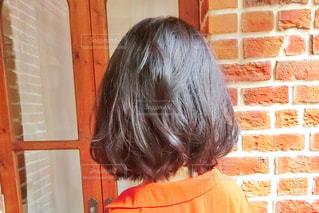 レンガ壁の前に立っているミディアムヘアの女性の写真・画像素材[1604317]