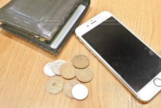 木製のテーブルの上に座って携帯電話の写真・画像素材[1630590]