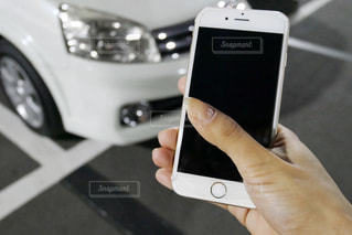 車両前で携帯電話を持つ手の写真・画像素材[1639314]