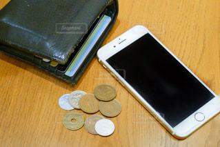 木製テーブルの上に座っている携帯電話の写真・画像素材[1647414]