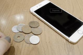 木製テーブルの上の携帯電話の写真・画像素材[1647415]