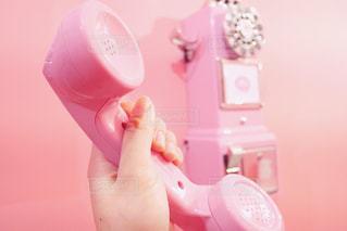 ピンクの受話器を持っている手の写真・画像素材[1654146]