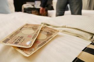 ホテルのベッドの上にあるお金と奥にいる男性の影の写真・画像素材[1659885]