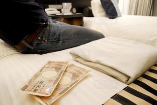 ホテルのベッドの上に座っている人とお金の写真・画像素材[1659886]