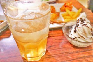 コーヒー カップの横にあるオレンジ ジュースのガラスの写真・画像素材[1674174]