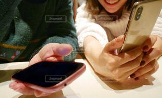 スマホを操作を教える為にテーブルに座っている女性達の写真・画像素材[1708192]