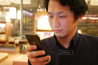 携帯電話を見てテーブルに着席した人の写真・画像素材[1740446]