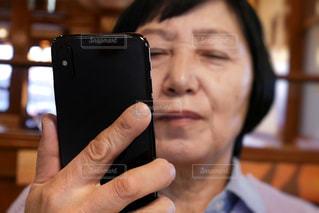 目が悪い、携帯電話を持つ高齢の女性の写真・画像素材[1799996]