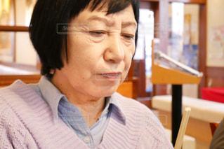 レストランのテーブルに座っている年配の女性の写真・画像素材[1801824]