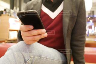 身に着けているスーツとネクタイの携帯電話を保持している人の写真・画像素材[1836715]