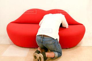 赤いソファーに座っている人の写真・画像素材[2105938]