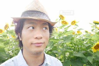 帽子をかぶって、カメラで微笑んでいる若い男の写真・画像素材[2105951]