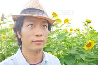 帽子をかぶって、カメラで微笑んでいる若い男の写真・画像素材[2105952]