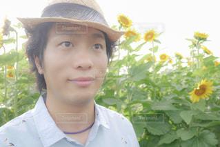 帽子をかぶって、カメラで微笑んでいる若い男の写真・画像素材[2105953]