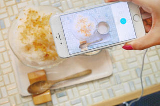 テーブルの上の食べ物とスマホの写真・画像素材[2109243]