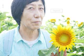 黄色い花をかぶった男の写真・画像素材[2110469]